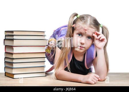 Portrait of beautiful girls with glasses shifted his hand to his forehead, oblakotivsheysya on the table with books - Stock Photo