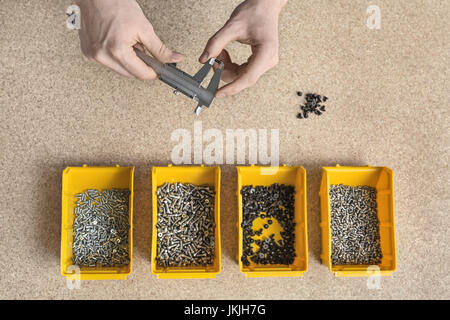 Plastic boxes with screws and male hands - Stock Photo