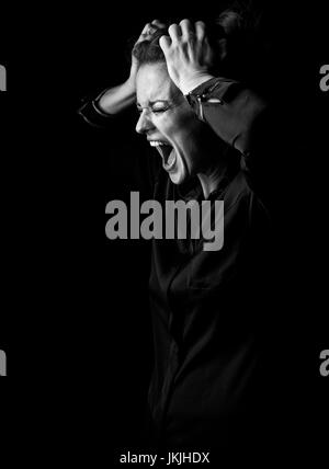 Сoming out into the light. Portrait of angry woman in the dark dress isolated on black background - Stock Photo