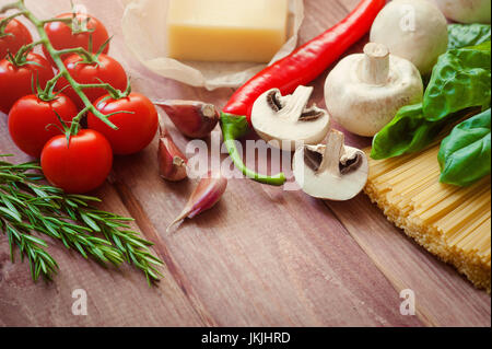 bunch of Italian spaghetti closeup with mushrooms and tomatoes on a rustic kitchen on a wooden table. In background - Stock Photo