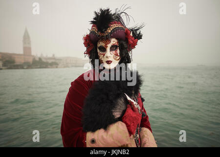 Female Mask wearer at the Carnival of Venice with red Coat and Red dress - Stock Photo