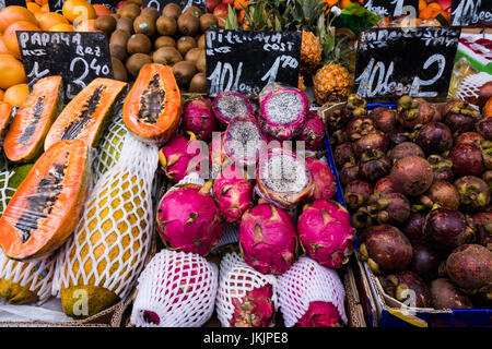 A variety of fresh and exotic fruit and vegetables in display for sale in a street market - Stock Photo