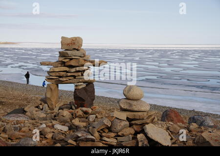 Inukshuk or Inuksuk on a rocky beach with ice on the ocean in late June in the high arctic near the community of - Stock Photo