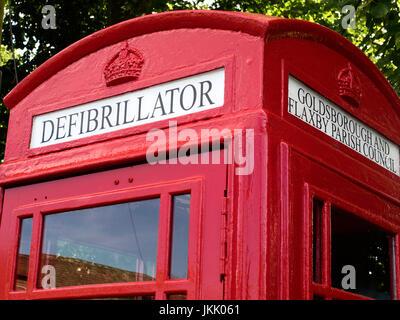 Defibrillator Sign in an Old K6 Red Telephone Box at Goldsborough near Knaresborough North Yorkshire England - Stock Photo