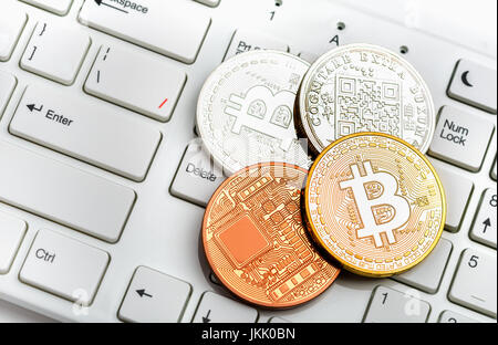 Bitcoin coins gold and silver on white keyboard background - Stock Photo