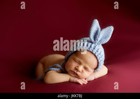 Little Girl Sleeping Curled Up On A Red Chair Stock Photo