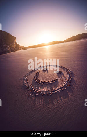 Smiling face drawn on a sandy beach with sundown in the background. - Stock Photo