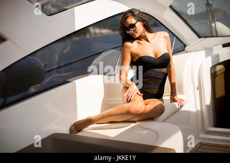 Pretty young woman relaxing on the yacht at sunny day - Stock Photo