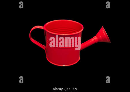 Single Red Watering can Isolated on Black Background. Image is clean and bright and centred in the image with room - Stock Photo