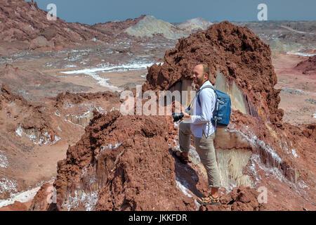 Hormuz Island, Hormozgan Province, Iran  - Tourist hike up the steep track on salty mountains, one backpacker admiring - Stock Photo