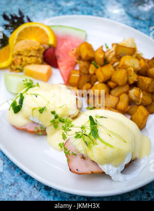 Classic Eggs Benedict (soft poached eggs, Canadian back bacon, and Hollandaise sauce on an English muffin), fried - Stock Photo
