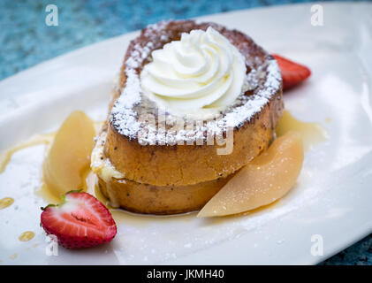 Beautifully plated cinnamon French toast (eggy bread) with whipped cream, maple syrup, vanilla poached pears, and - Stock Photo