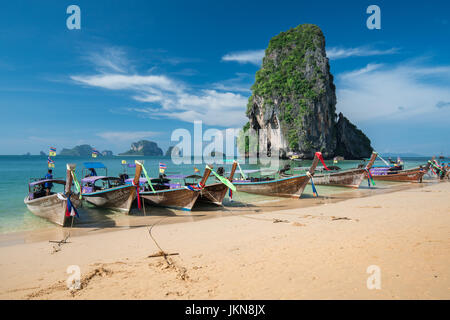 KRABI, THAILAND - DECEMBER 5 : Colorful long tail boats at beautiful Ao Nang beach on a background of blue sky and - Stock Photo