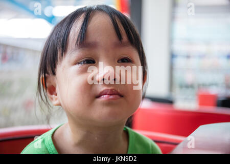 Asian Chinese little girl sitting in chair and crying - Stock Photo