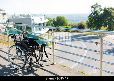 Black new wheelchair left on a terrace - Stock Photo