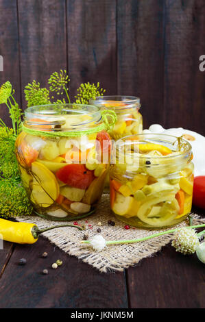 Pickles: vegetable assortment (zucchini, pepper, carrots, tomato, green peas) in glass jars on a dark wooden background. - Stock Photo