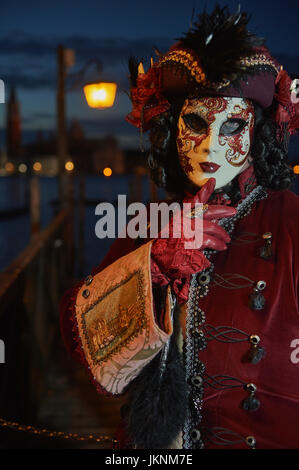 Female Mask wearer at the Carnival of Venice with red Coat and Red ...