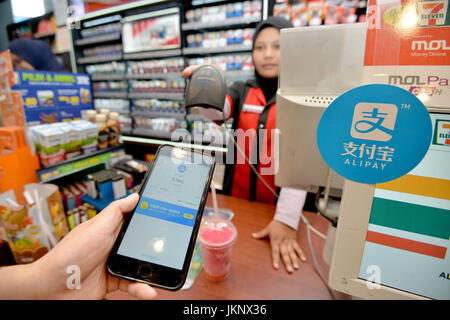 (170724) -- KUALA LUMPUR, July 24, 2017 (Xinhua) -- A customers uses Alipay to pay for his pill at a shop in Kuala - Stock Photo