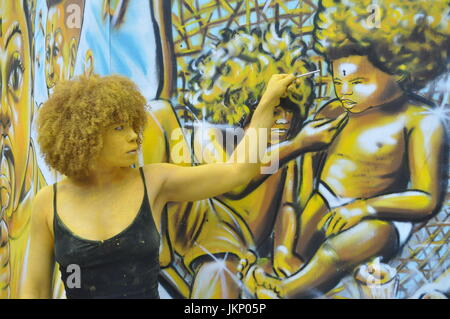 Today Brick Lane saw a different type of art as some of the artwork came to life in the form of artist Holly Oluwo - Stock Photo