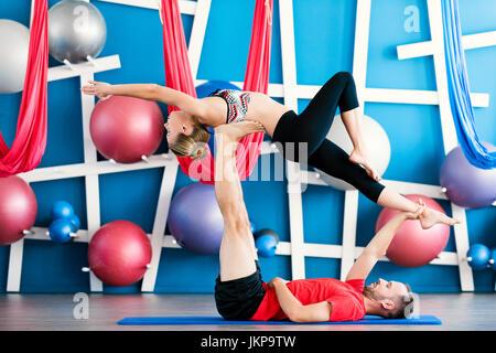 Couple practicing acro yoga in a studio. Acro yoga concept. Couple yoga class workout - Stock Photo