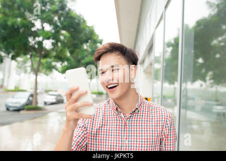 Cheerful handsome man checking something on mobile phone - Stock Photo