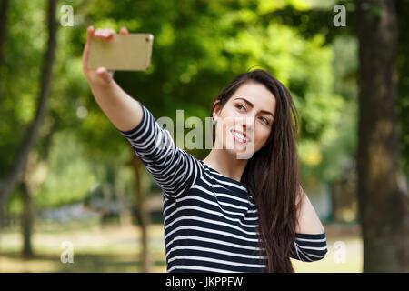 girl taking selfie outdoors - Stock Photo
