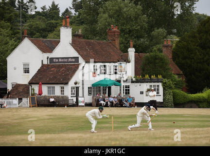 Spectators sat outside the Barley Mow pub enjoying a village cricket match between Tilford and Grayswood being played - Stock Photo