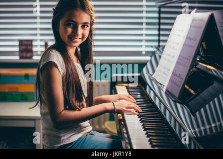 Happy girl smiling for the camera as she plays piano in her bedroom. - Stock Photo