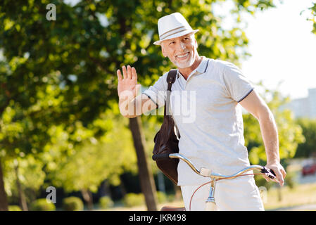 Positive delighted man waving his right hand - Stock Photo