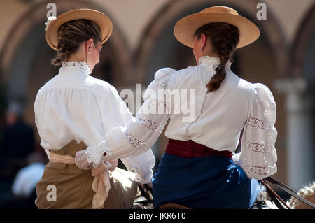 Italy, Lombardy, Crema, Woman in Traditional Costume Riding Horse - Stock Photo