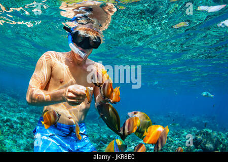 Happy family vacation - man in snorkeling mask dive underwater with tropical fishes in coral reef sea pool. Travel - Stock Photo