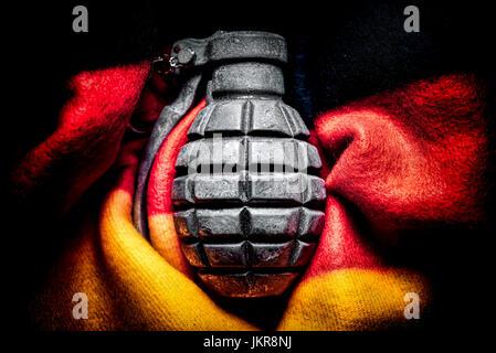 Grenade in Germany flag, extremism and terror danger in Germany, Handgranate in Deutschlandfahne, Extremismus- und - Stock Photo
