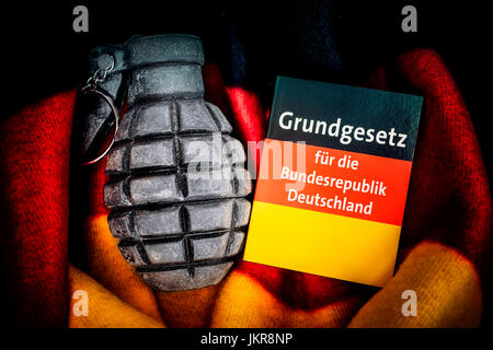 Grenade in Germany flag and basic law, extremism and terror danger in Germany, Handgranate in Deutschlandfahne und - Stock Photo