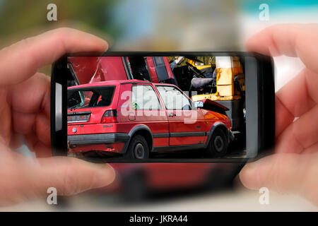 Onlooker takes a photo of traffic accident, of symbolic photo, Schaulustiger fotografiert Verkehrsunfall, Symbolfoto - Stock Photo