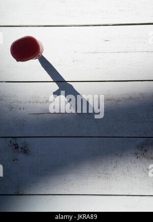 Directly above shot of knife on wooden table in shadow - Stock Photo