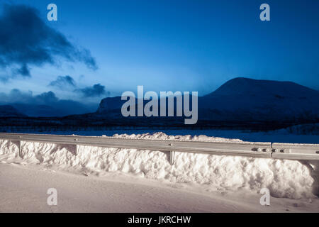 Railing on snow covered mountains against blue sky at night, Nikkaluokta, Sweden - Stock Photo