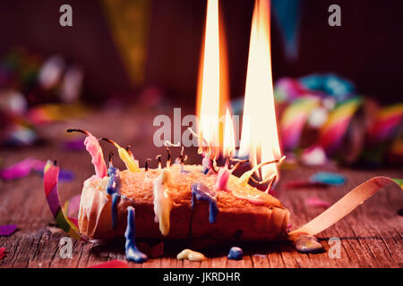 a small cake topped with some lit candles and some other unlit candles after blowing out the cake, on a rustic wooden - Stock Photo