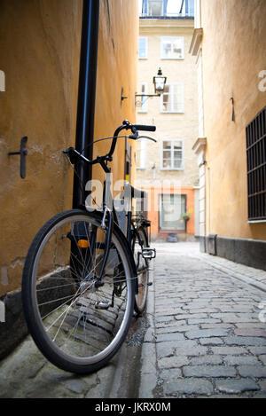 vintage retro bike parked on old cobbled alley, stockholm sweden - Stock Photo
