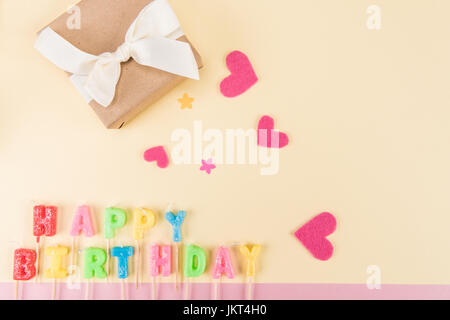top view of happy birthday lettering, gift box and paper hearts on beige, birthday party concept - Stock Photo