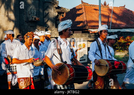 Bali, Indonesia - March 07, 2016: Balinese traditional musicians play the gamelan at the ceremonial procession during - Stock Photo