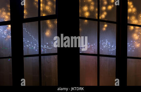 Christmas lights through a window - Stock Photo