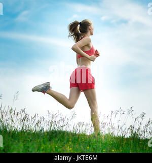 Young lady running. Woman runner running through the summer park rural road. Workout in a park. Beautiful fit girl. - Stock Photo