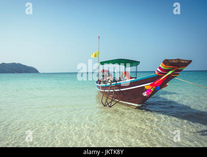 A boat is anchored at Bottle Beach, Koh Pha Ngan, Thailand. Southeast Asian travel, through the scenic islands of - Stock Photo