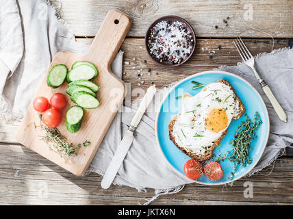 Breakfast set. Whole grain sandwich with fried egg, vegetables and herbs - Stock Photo