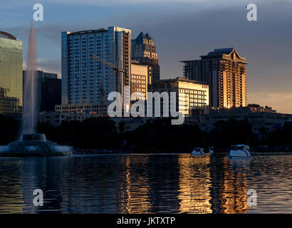 Swan shaped paddle boats at Lake Eola Park with the downtown Orlando skyline in the background on the Fourth of - Stock Photo