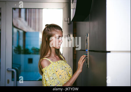 woman dials an apartment code on an electronic doorphone panel - Stock Photo