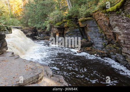 The Sturgeon River flows rapidly over Canyon Falls near L'Anse Michigan. Autumn colors and canyon walls in the background - Stock Photo