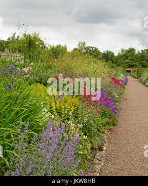 Colourful English cottage garden with pathway leading past herbaceous border with masses of red, white, yellow and - Stock Photo