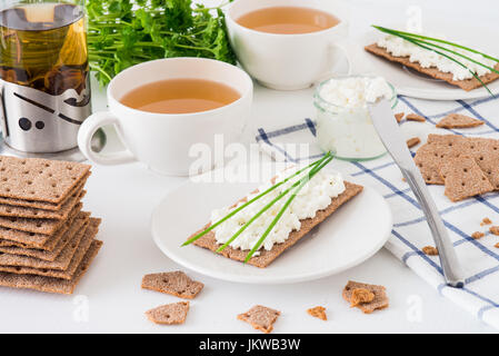 Snack with fresh tea and rye crispy bread (Swedish crackers) with cottage cheese, decorated with thin green onion, - Stock Photo