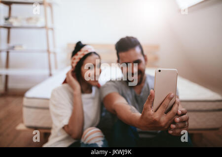 Shot of young couple sitting at home and taking selfie with mobile phone. Focus on smart phone in hands of a man. - Stock Photo